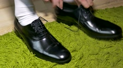 Man in white dress socks  to tie shoelaces shoes Stock Footage