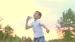 Happy boy with paper airplane on the field over sunset background Stock Footage