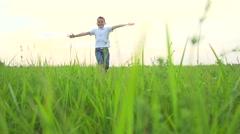 Happy kid running on summer green field. Joyful boy enjoying nature outdoor Stock Footage
