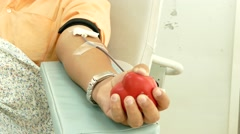 donor squeezes the ball in his hand - stock footage