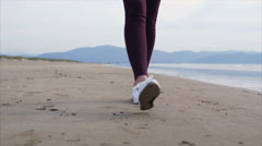 Low section of woman's feet walking on beach - stock footage