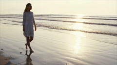 Young woman walking on sea shore during sunset Stock Footage