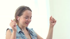Pretty teenage girl sitting on sofa, listening music with headphones and dancing - stock footage