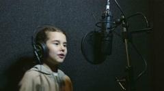 Girl teen in headphones singing into microphone recording studio Stock Footage