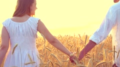 Couple walking on golden wheat field and holding each other's hands over sunset Stock Footage