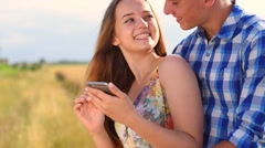Beautiful happy young couple on wheat field smiling and using smartphone togethe Stock Footage