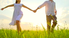 Happy young couple holding hands run through a wide field, having fun outdoors Stock Footage