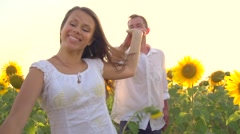 Happy couple running on sunflower field, taking hands and smiling Stock Footage