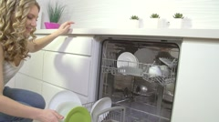Young woman washing dishes in dishwashing machine Stock Footage