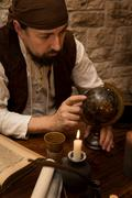 Medieval man pointing at a old globe, concept travelling and tourism - stock photo