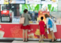 Blurred people buying a drink and food at counter - stock photo