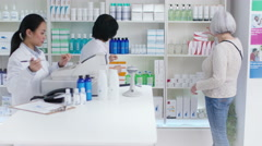 4K Friendly pharmacy worker advising senior woman which medication to take - stock footage