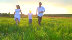 Happy family running on the field over sunset background - stock footage