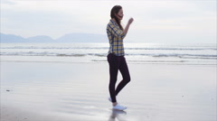 Slow motion tracking shot of young woman walking on beach Stock Footage