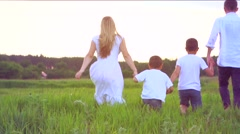 Happy joyful young family with two children running on summer field Stock Footage
