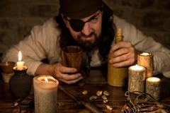 grumpy pirate with a bottle of rum sitting on a medieval table - stock photo