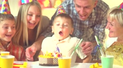Little boy blows out candles on birthday cake at party Stock Footage