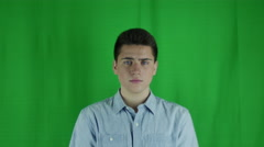 Young man is nervous in front of a greenscreen in a blue shirt Stock Footage