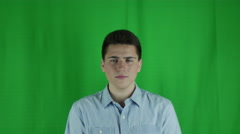 Young man is sad in front of a greenscreen in a blue shirt Stock Footage
