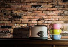 Colorful tiffin carrier and toaster on wooden cupboard with vintage brick wal - stock photo