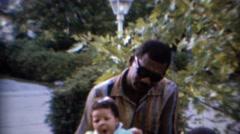 1967: African American man holding sleepy curly hair baby. CARMEL, INDIANA Stock Footage