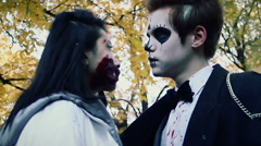 Young couple kissing at Halloween party, man and woman in zombie suits have fun Stock Footage