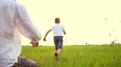 Father and son playing with paper airplane outdoors Stock Footage