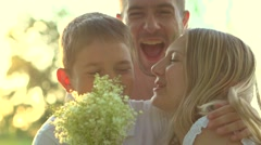 Happy family with bouquet of flowers outdoors Stock Footage