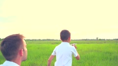 Father and son playing with paper airplane on the field Stock Footage