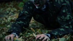 Injured man wearing military uniform crawling in wild forest, looking for help Stock Footage