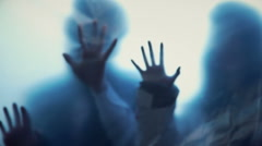 Human silhouettes behind transparent film stretching hands, scary nightmare Stock Footage