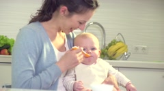 Mother feeding her baby girl with a spoon Stock Footage