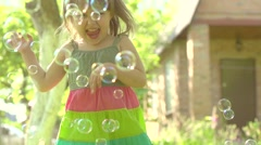 Happy little girl playing wit soap bubbles outdoor Stock Footage