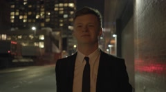 Caucasian businessman walking in the city street at night. shot on red epic Stock Footage