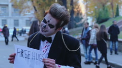 Young man in zombie suit holding free hugs sign in hands, smiling in camera - stock footage