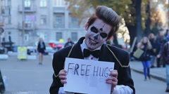 Young men in zombie suits hugging in street, funny flash mob on Halloween Stock Footage