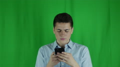 Young man is looking at phone in front of a greenscreen in a blue shirt Stock Footage