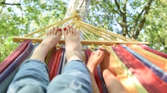 Mother and her baby resting on a hammock and move their bare feet Stock Footage