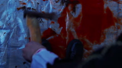 Crazy murderer dropping axe in pool of blood, leaving crime scene, horror film - stock footage