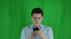 Young man is distracted on phone and looks up annoyed in front of a greenscreen Stock Footage