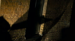 Shadows of terrible zombies walking slowly along old brick building in darkness Stock Footage
