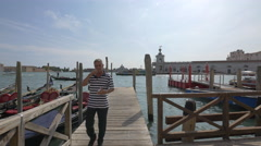 Gondolier walking on a wooden pier in Venice Stock Footage