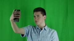 Young man takes selfies in front of a greenscreen in a blue shirt Stock Footage