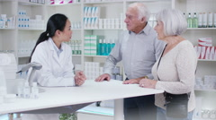 4K Friendly pharmacy worker advising senior couple which medication to take Stock Footage