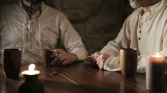 Two medieval looking men are gambling Stock Footage