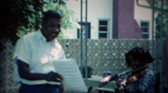 1967: African American daughter practicing violin with her father. CARMEL, Stock Footage