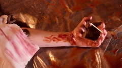 Human hand convulsing in pool of blood, crazy psycho maniac dissecting victim Stock Footage