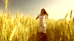 Beauty girl with healthy long hair running and laughing on wheat field. Stock Footage