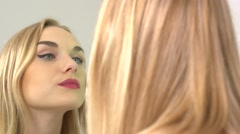 Beauty blonde model girl looking in the mirror and applying make up. Stock Footage