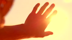 Human hand touching the sunlight by hand over beautiful sky background. Stock Footage
